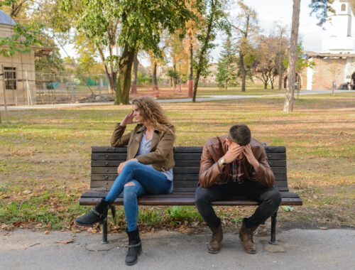 woman and man sitting on brown wooden bench